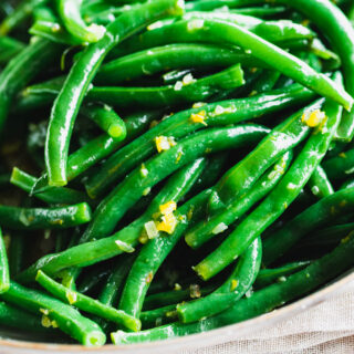 close up of green bean with orange zest on them