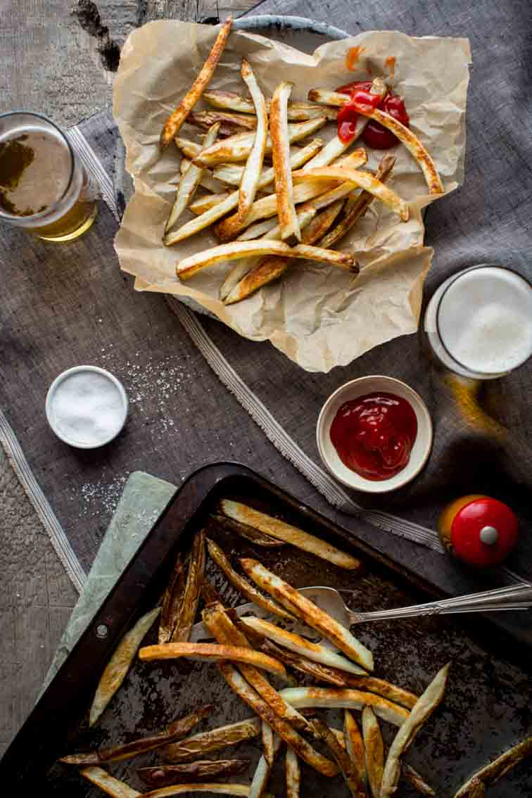 Skinny Oven Fries on baking tray and in parchment paper