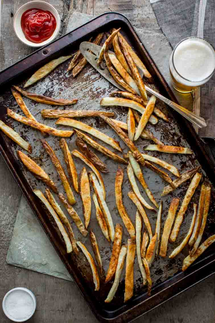 Skinny Oven Fries on baking tray next to ketchup