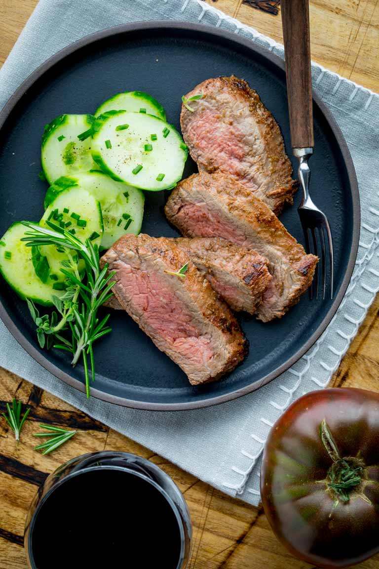 steak and cucumbers on a black plate