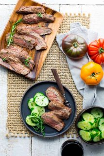 a platter of flank steak and a plate with cucumbers and steak