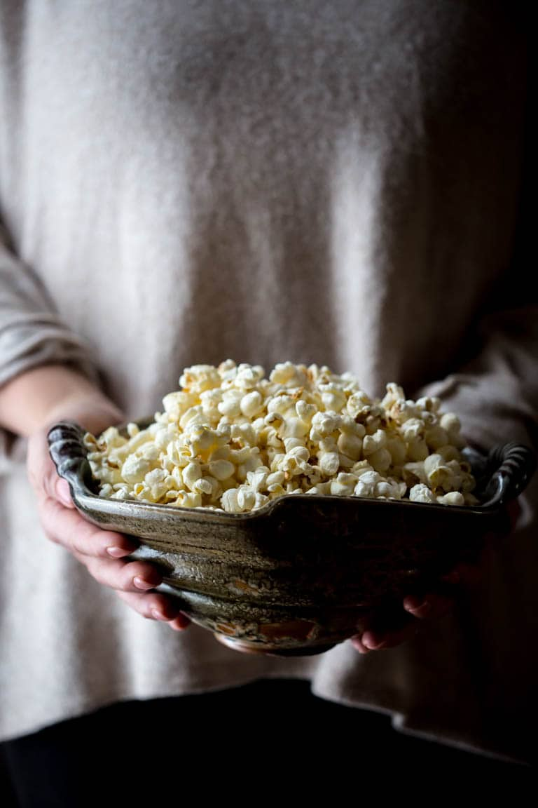 holding a large bowl of stovetop popcorn