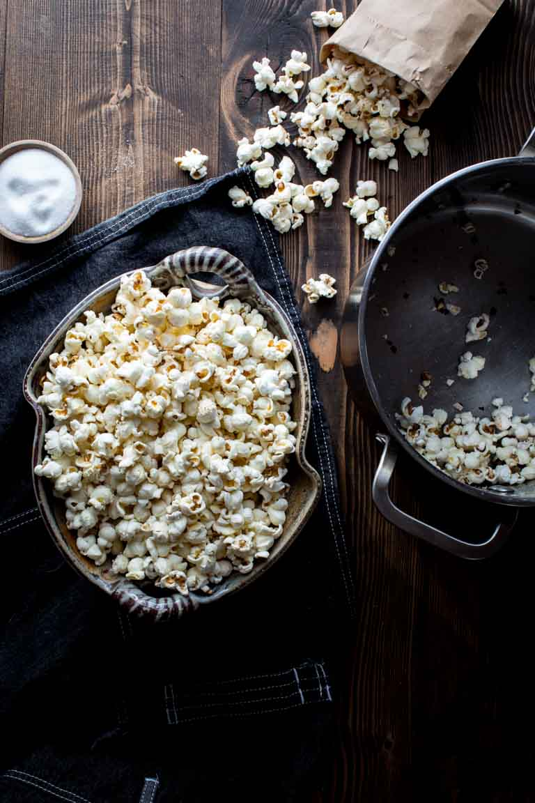 stovetop popcorn in a bowl next to a bag of popcorn