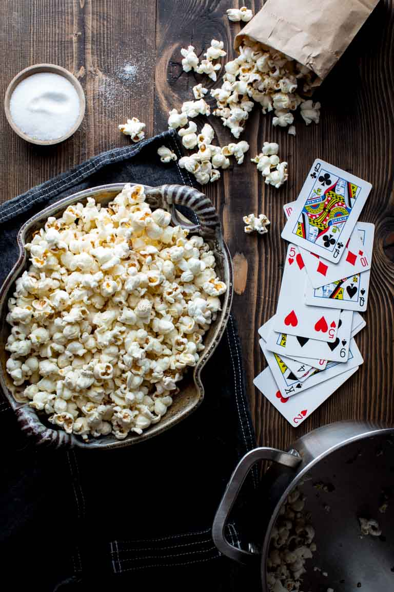 stovetop popcorn in a large bowl next to playing cards