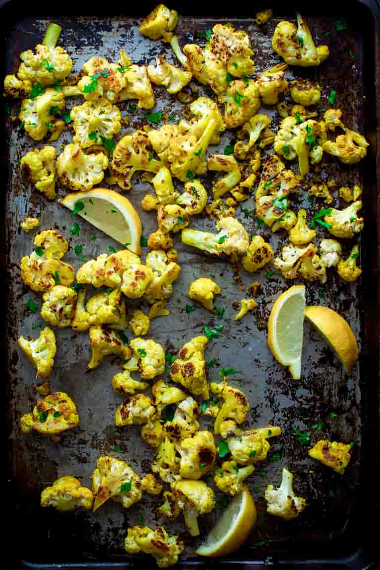 a baking sheet with curry cauliflower on it and lemon wedges