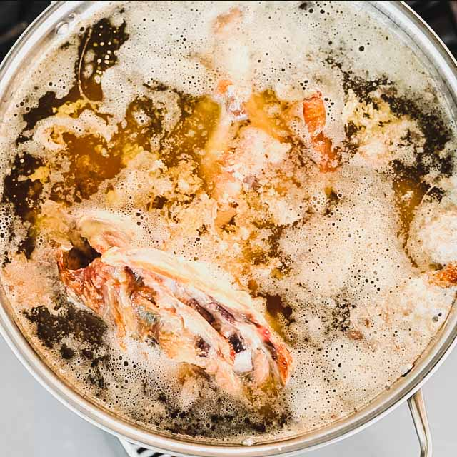 a pot of stock on the stove with foam and fat collecting on the top.
