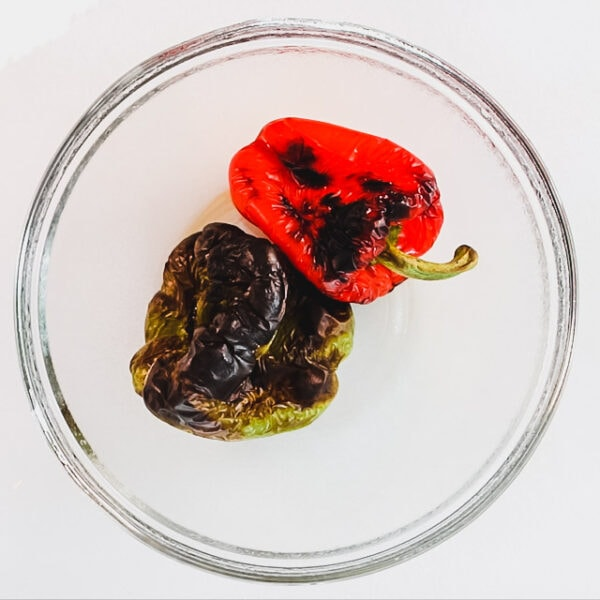two blackened peppers in a bowl