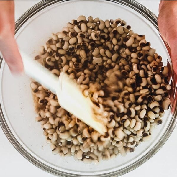 stirring black-eyed peas in the bowl with the dressing