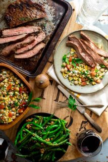 a table scape with a tray of grilled steak, green beans, a bowl of corn salad and a plate with both from overhead