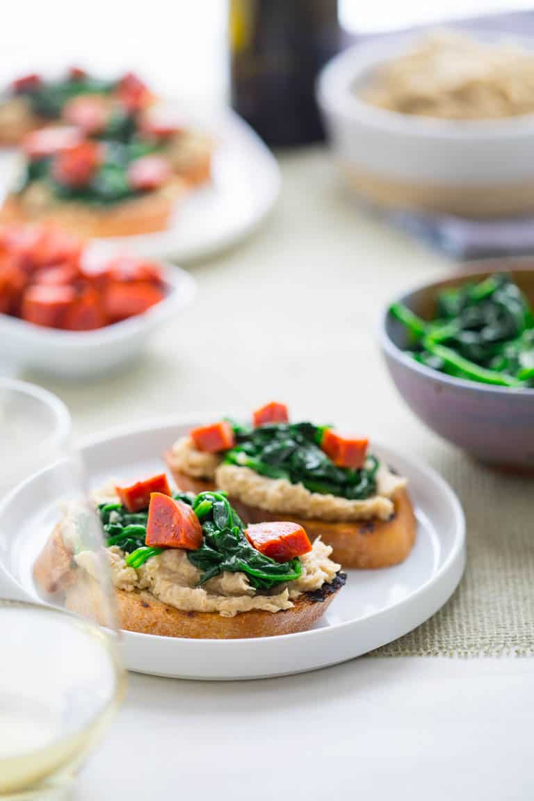 These super versatile and yummy White Bean Bruschetta with Garlicky Greens are the perfect little appetizer for your Spring and Summer get-togethers. | Healthy Seasonal Recipes | Katie Webster
