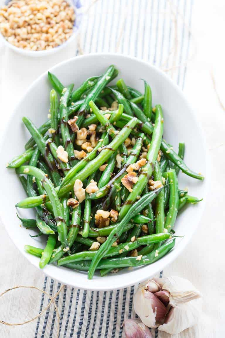 balsamic green beans with walnuts next to garlic clove