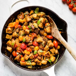 cherry tomato panzanella in a skillet with a wooden spoon