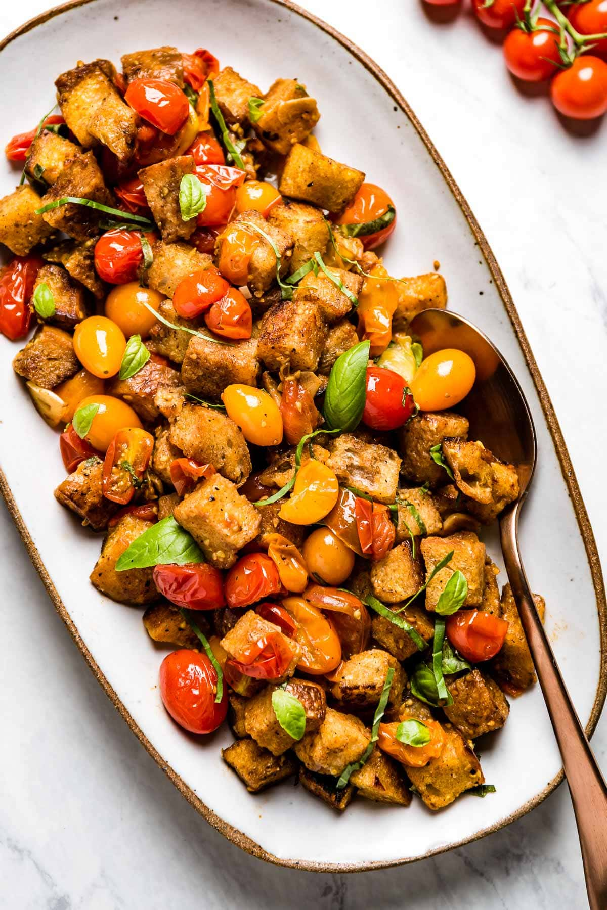 a platter with cherry tomato panzanella