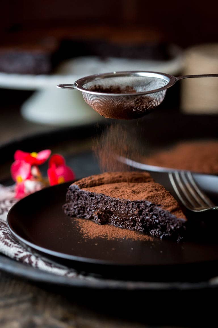 dusting cocoa powder onto a slice of Flourless Chocolate Cake