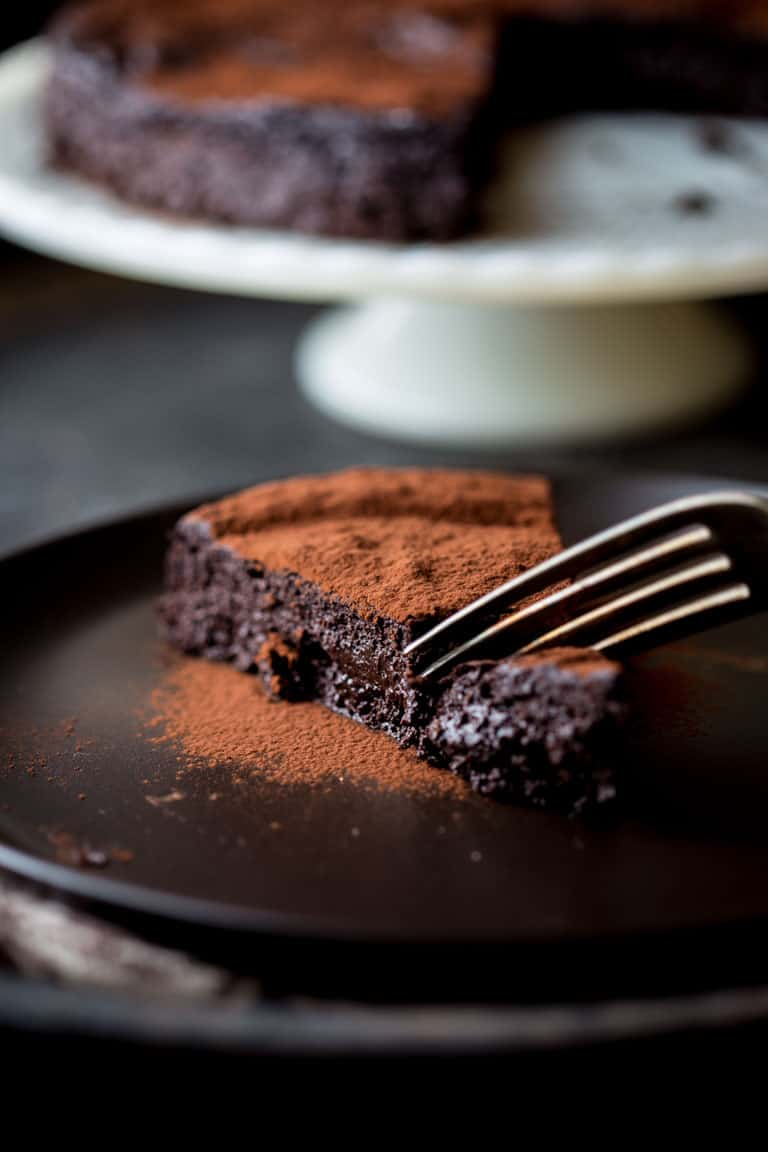cutting into a piece of Flourless Chocolate Cake with a fork