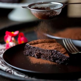 A close up of a piece of chocolate cake on a plate, with Flour