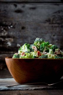 a side view of a wooden bowl heaped with broccoli salad with bacon