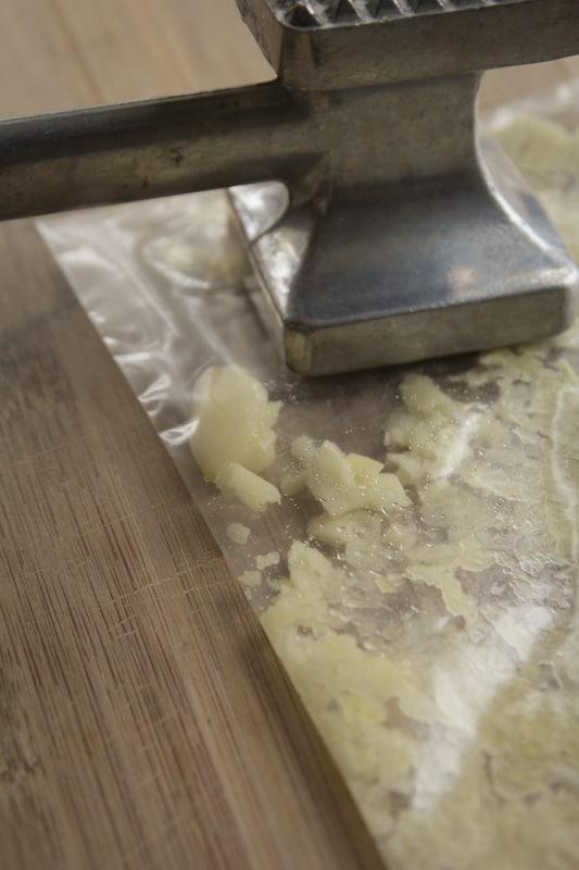 mashing the garlic in the bag to make the marinade