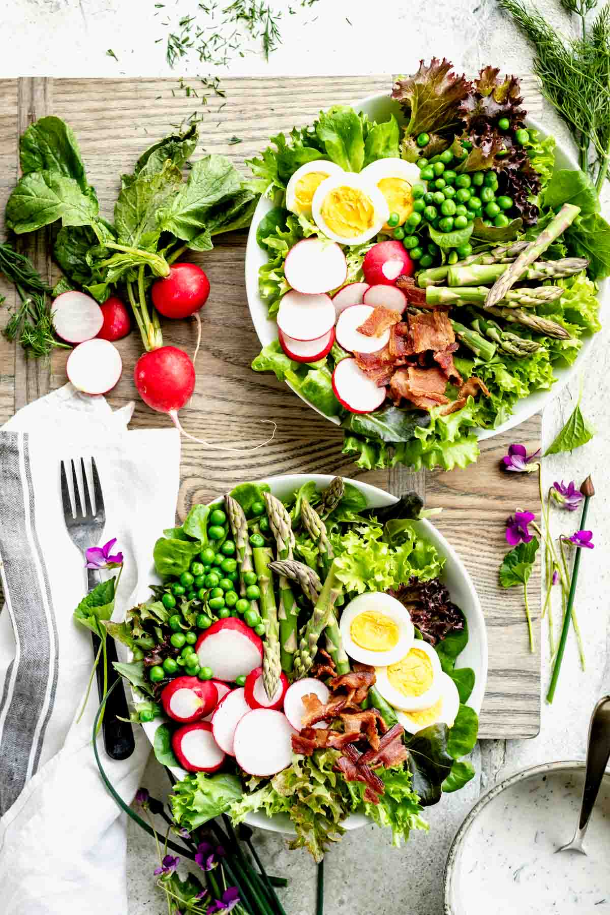 Spring Salad in two bowls on a gray cutting board from overhead