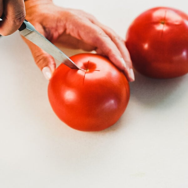 """Score an """"x"""" mark at the bottom of each tomato"""