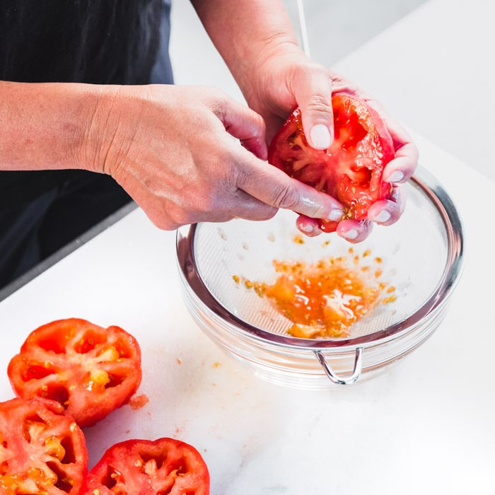 removing tomato seeds over a sieve