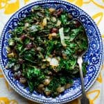 A blue china dish with sauteed kale in it, on a yellow and white dish towel
