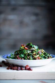 Side view of a bowl of kale with cranberries and balsamic vinegar on a gray table with a gray background