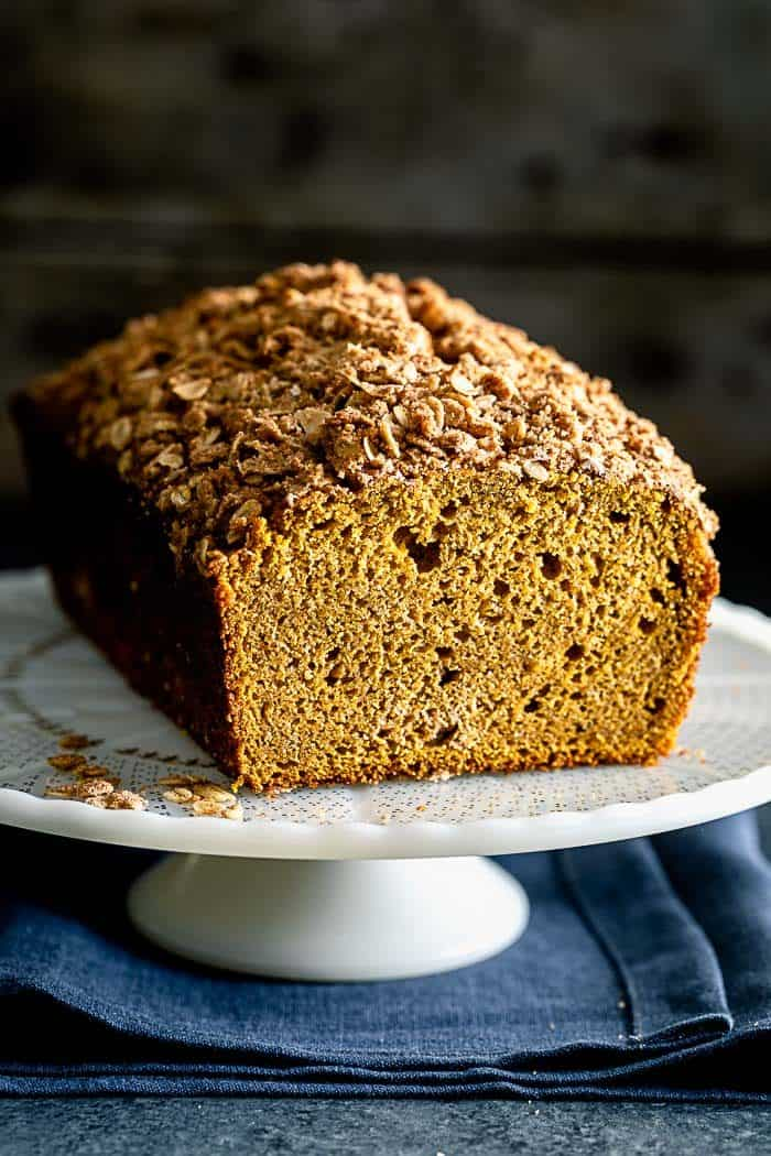 A loaf of pumpkin streusel bread on a cake stand, with a slice removed to reveal the texture of the crumb