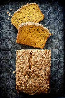 A loaf of pumpkin streusel bread, cut into slices and laid on a black patterned baking sheet