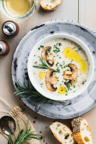 Cream of mushroom soup in a white bowl set on a gray pie plate on a brownish gray wooden tabletop