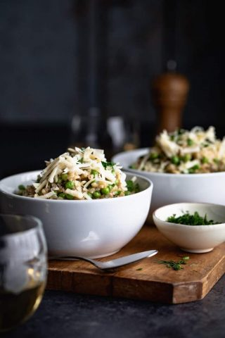 A side view of two bowls of brown rice risotto with peas and topped with white cheddar cheese