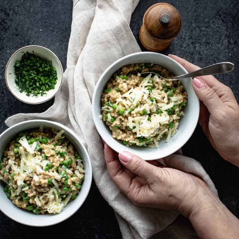 An overhead view of two bowls of brown rice risotto on a black countertop with a tan linen napkin and two hands grabbing a bowl