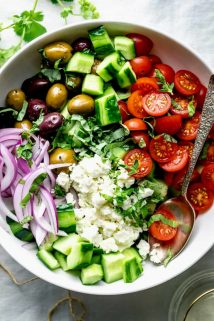 A close up view of a white bowl filled with Greek Cucumber Salad