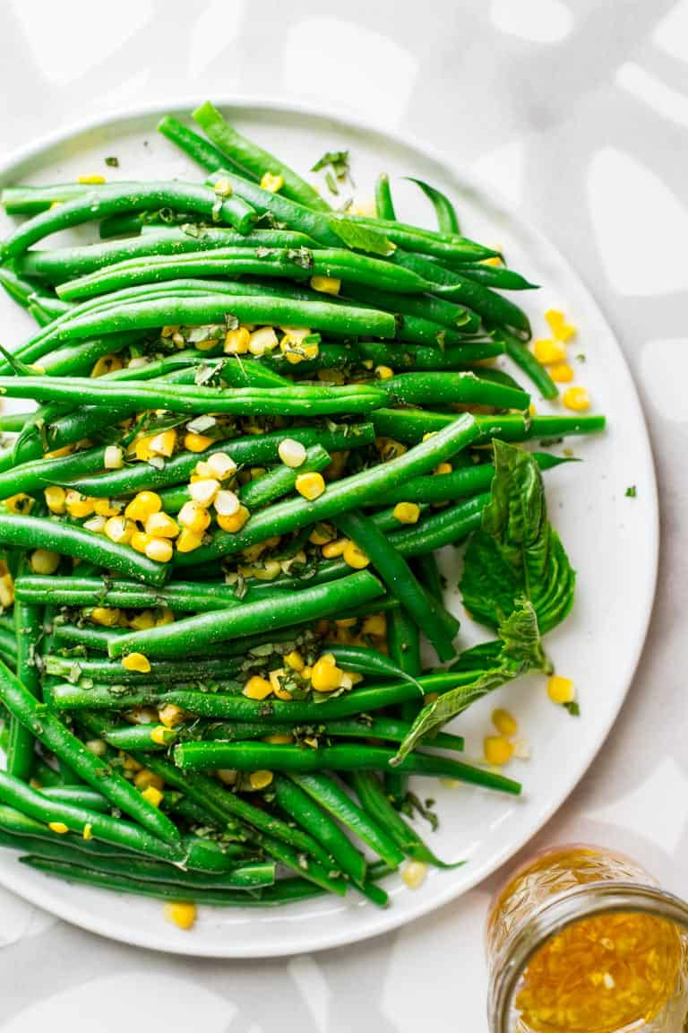 Simple salad made with green beans and sweet corn with cider vinegar and shallot dressing with fresh chopped basil. An easy vegan side salad. 7 Grams Net Carbs. Healthy Seasonal Recipes by Katie Webster. #glutenfree #vegan #corn #greenbeans #sidesalad #grainfree #dairyfree #healthy
