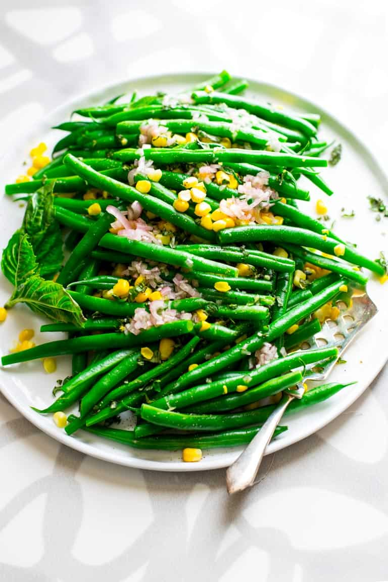 Simple salad made with green beans and sweet corn with cider vinegar and shallot dressing with fresh chopped basil. An easy vegan side salad. Healthy Seasonal Recipes by Katie Webster. #glutenfree #vegan #corn #greenbeans #sidesalad #grainfree #dairyfree #healthy