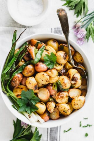 Overhead view of bowl of grilled potatoes with grilled scallions