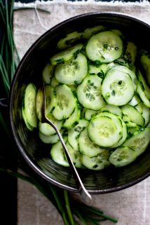 An overhead view of Healthy Cucumber Salad in a black bowl.