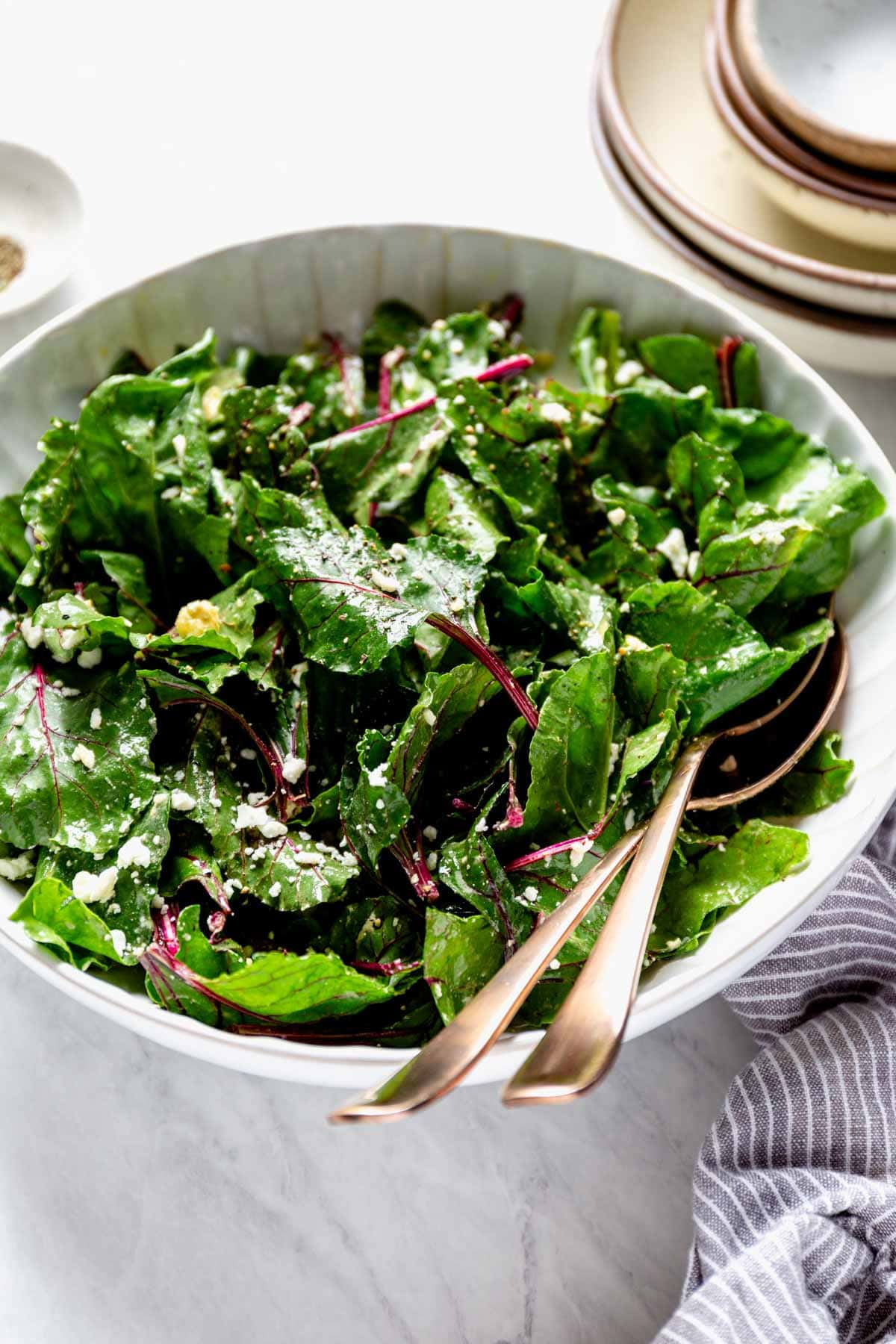 beet greens in a white bowl with tongs