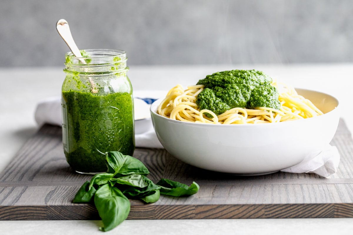 jar of pesto and pasta with pesto on top on a gray cutting board from the side