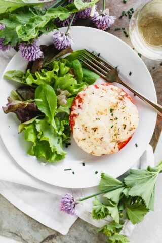 Roasted Tomato with melted white cheddar on top on a plate with greens and chive blossoms