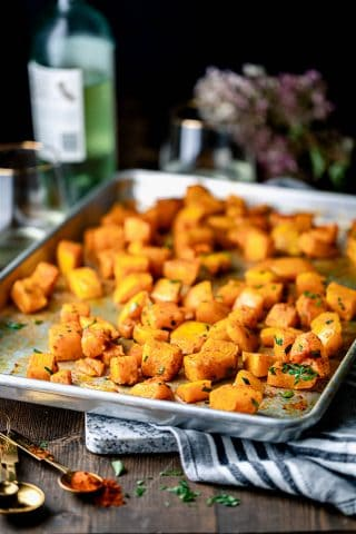 A sheet pan of roasted butternut squash with a bottle of white wine and a bouquet of sedum