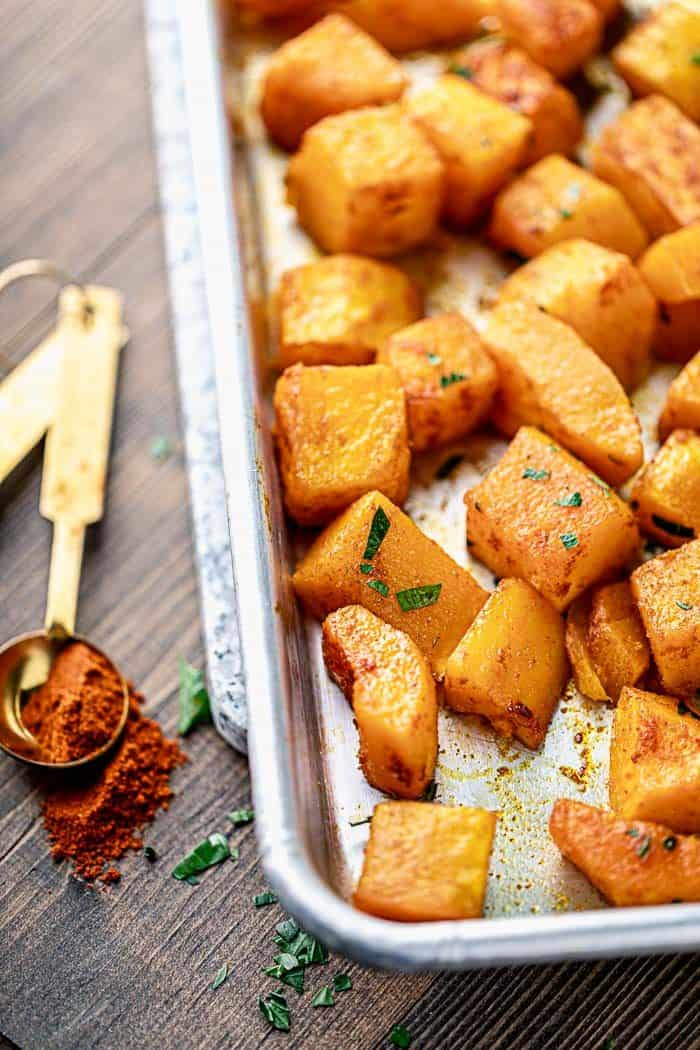 a close up of roasted butternut squash with smoked paprika on a sheet pan