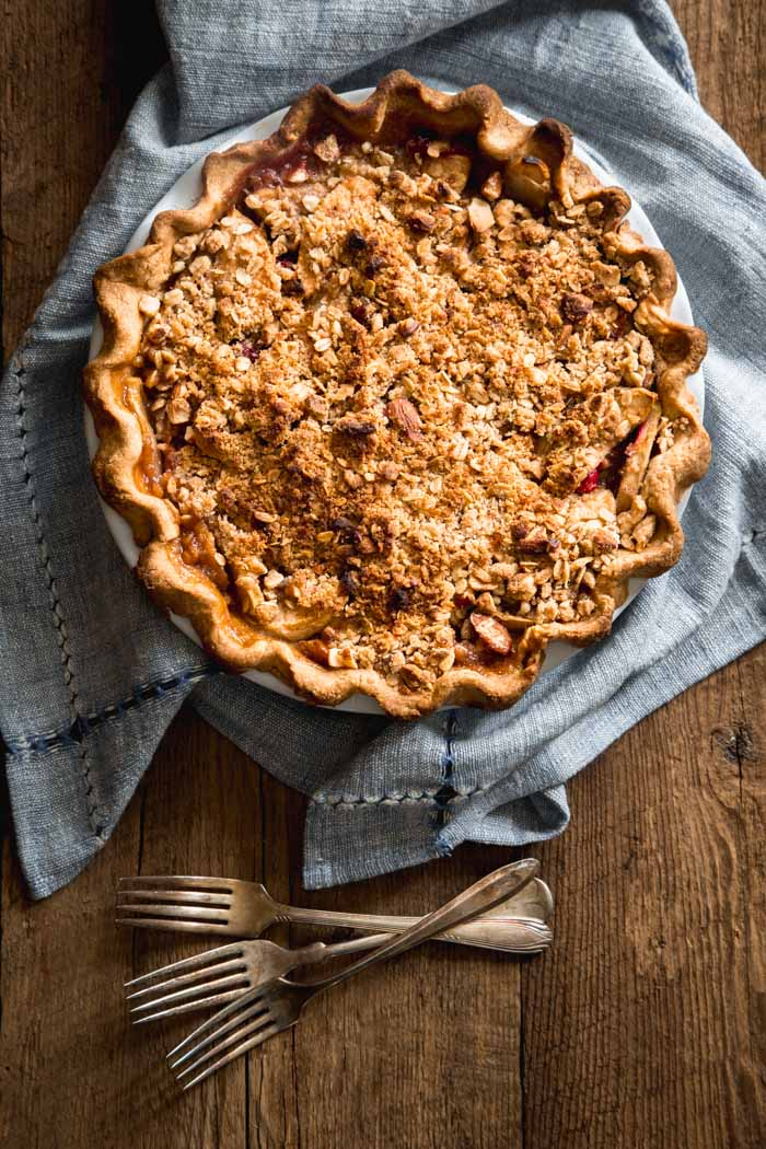 Apple Crumb Pie overhead on a blue napkin with forks