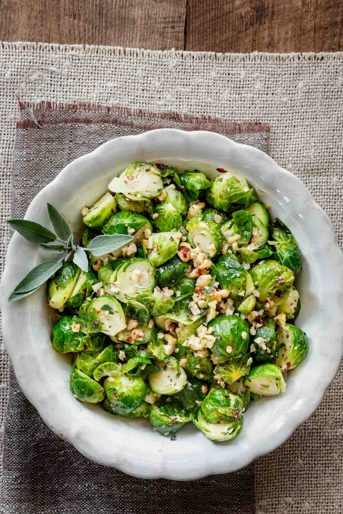 brussels sprouts with hazelnuts in a white bowl on a rustic tan linen