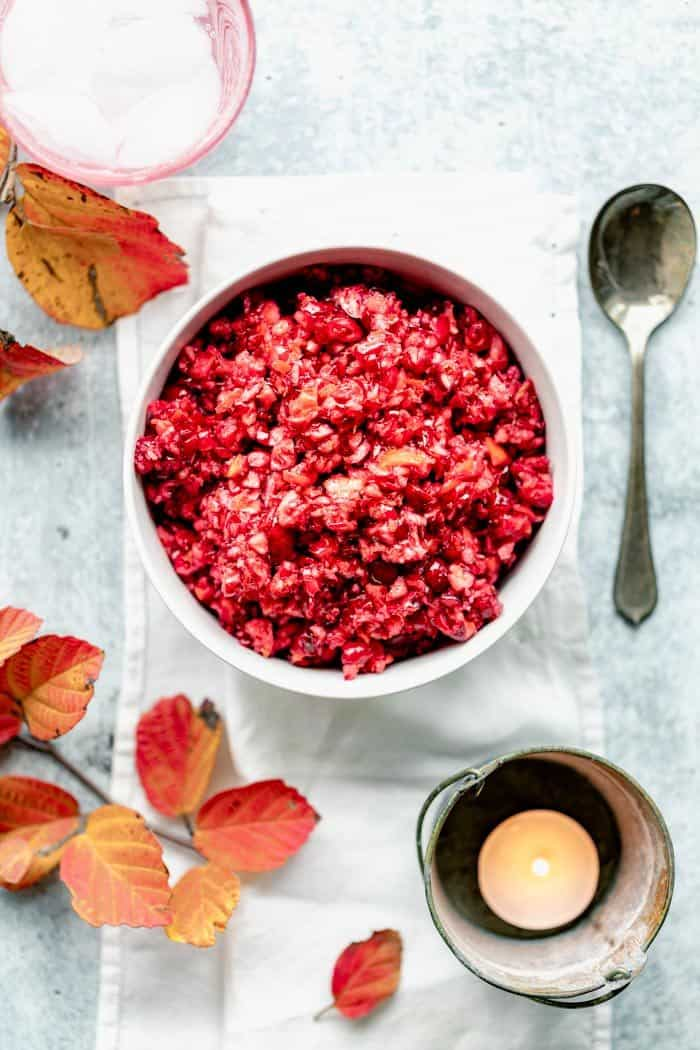 Raw cranberry relish in a white bowl on a blue gray table with orange foliage and a votive candle