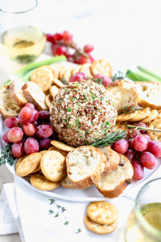 side view of cheeseball on a platter with crackers and grapes