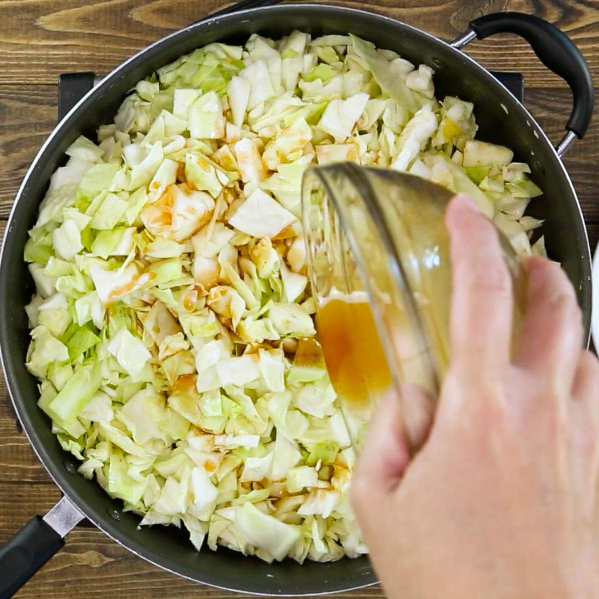 adding the sauce to the cabbage in a skillet