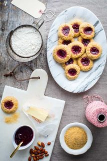 Jam Thumbprint Cookies on a platter surrounded by baking ingredients, red and white twine and gift tags