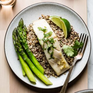 cod on quinoa with a fork and lime wedges from overhead
