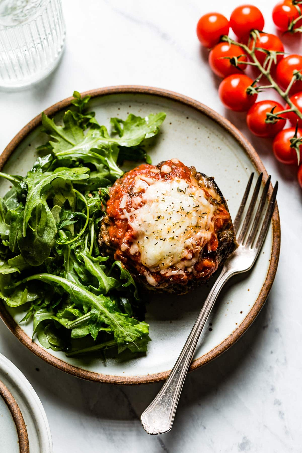 a plate with arugula salad and stuffed mushroom with tomato sauce and cheese melted on top